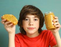 与坚果的青春期前的男孩举行花生酱编结 免版税库存图片