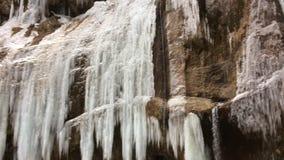 与垂悬从岩石的巨大的美好的冰柱的冻瀑布 影视素材