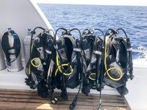 与垂悬在一条快行小船的一个立场的水管和潜水者,船,在一种热带手段的巡航划线员的很多黑潜水服 库存照片