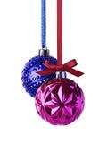 与垂悬在丝带的弓的紫色和蓝色圣诞节球 免版税图库摄影