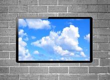 与垂悬在墙壁上的蓝天的黑屏LCD电视 免版税图库摄影
