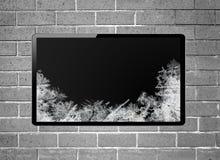 与垂悬在墙壁上的霜屏幕的黑屏LCD电视 免版税库存照片