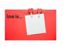 与垂悬在晒衣绳的晒衣夹的红色心脏隔绝在白色背景 库存照片