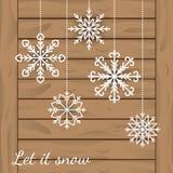 与垂悬在木板条的白色雪花的抽象冬天背景 库存图片