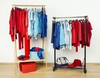 与垂悬在机架的红色和蓝色衣裳的衣橱恰好被安排 免版税库存图片