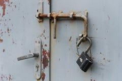 与垂悬在门闩的开放挂锁的老门 被设置的背景 免版税库存图片