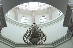 与垂悬在玻璃圆顶的一个金黄链子的圆的渐暗的光线 免版税库存照片