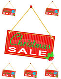 与垂悬在a的题字圣诞节销售的红色标志标签 免版税库存照片