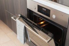 与垂悬对此的灰色毛巾的被打开的烤箱 免版税图库摄影