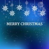 与垂悬的白色雪花装饰和文本圣诞快乐的圣诞节蓝色背景 库存图片