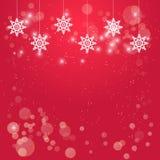 与垂悬的白色雪花装饰的圣诞节红色背景 免版税库存照片