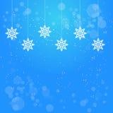 与垂悬的白色雪花装饰的圣诞节蓝色背景 库存图片