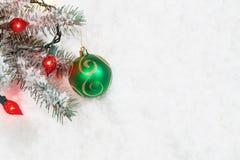 与垂悬从树枝的光的圣诞节装饰品 免版税库存图片
