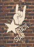 与垫铁姿态的摇滚明星标志在砖墙上 免版税图库摄影