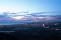 与城市光和一个沿海看法的晚上天空 免版税图库摄影