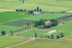 与培养的领域、农场和树的五颜六色的农村风景 免版税图库摄影