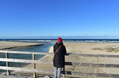 与基于木扶手栏杆和看看法的妇女的海滩 冬季衣服和红色帽子 好日子,有波浪的蓝色海 免版税库存图片