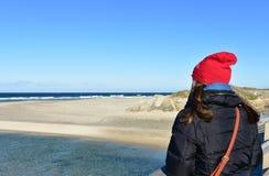 与基于木扶手栏杆和看看法的妇女的海滩 冬季衣服和红色帽子 好日子,有波浪的蓝色海 库存照片