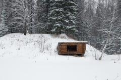 与堆的一个偏僻的木大厦在一个密集的森林,冬时里雪小屋 免版税库存图片