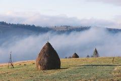 与堆的农村风景在山的领域的干燥干草 免版税库存图片