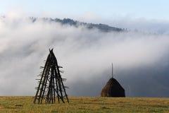 与堆的农村风景在山的领域的干燥干草 库存照片