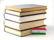 与堆的塔吉克斯坦旗子在白色背景的书 库存照片