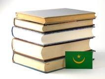 与堆的毛里塔尼亚旗子在白色背景的书 库存图片