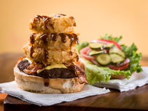 与堆的烟肉乳酪汉堡洋葱圈 免版税库存照片