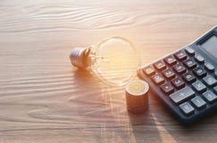 与堆的节能电灯泡硬币和计算器 免版税图库摄影