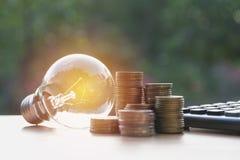 与堆的节能电灯泡硬币和计算器 免版税库存图片