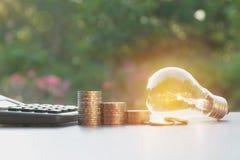 与堆的节能电灯泡硬币和计算器 库存照片