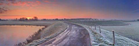 与堤堰的典型的荷兰风景,在日出的冬天 免版税图库摄影