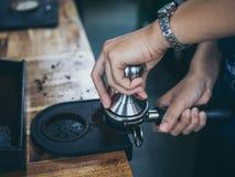 与堵塞器的专业barista手紧迫咖啡渣咖啡馆的 库存照片