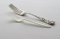 与塑料叉子的纯银叉子 免版税库存照片