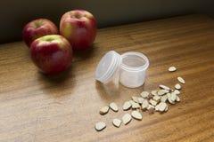 与塑料瓶子&切的杏仁的三个苹果 免版税库存照片