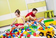 与塑料立方体的两座学龄前儿童修造城堡 库存图片
