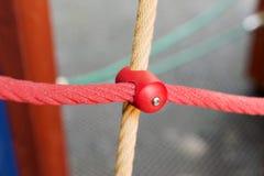 与塑料紧固的不同的色的绳索在操场 免版税库存图片