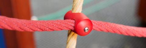 与塑料紧固的不同的色的绳索在操场 库存图片