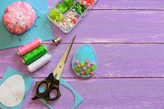 与塑料花和叶子的好的复活节彩蛋装饰品 毛毡蛋工艺,纸模板,在木背景的剪刀 免版税库存照片