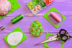 与塑料花和小珠的明亮的复活节彩蛋装饰 毛毡蛋工艺,剪刀,螺纹,纸模板,顶针 图库摄影