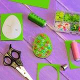 与塑料花和小珠的明亮的复活节彩蛋装饰 毛毡蛋工艺,剪刀,螺纹,纸模板,顶针 库存照片