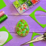 与塑料花的创造性的复活节彩蛋装饰 与花卉样式,剪刀,纸模板的毛毡鸡蛋 图库摄影