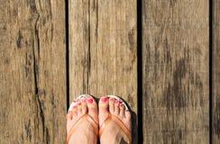 与塑胶人字平底拖鞋的女性英尺 免版税库存图片