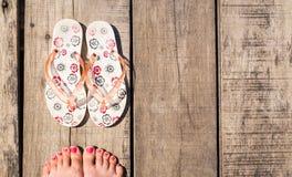 与塑胶人字平底拖鞋的女性英尺 图库摄影