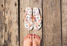 与塑胶人字平底拖鞋的女性英尺 免版税图库摄影