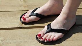 与塑胶人字平底拖鞋红色钉子的女性英尺 免版税库存图片