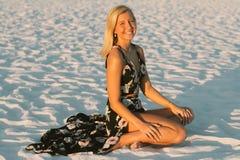 与塑造外面由海滩的金发的有吸引力的逗人喜爱的年轻女性模型 免版税库存图片