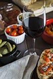 与塔帕纤维布盘和红酒的木饭桌集合 库存图片