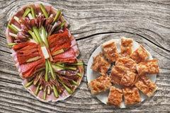 与塞尔维亚人Gibanica乳酪在老被打结的破裂的木庭院表上设置的饼切片的开胃菜美味盘 库存照片