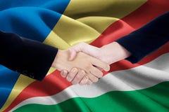 与塞舌尔群岛的旗子的合作握手 库存图片